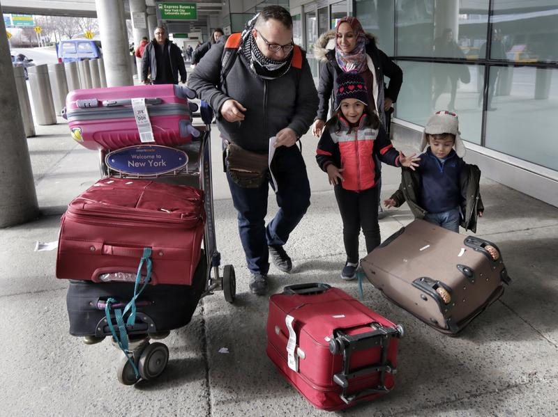 Munther Alaskry, accompanied by his wife Hiba, son Hassan and daughter Dima, gather their luggage as they leave JFK International Airport, in New York City, on Feb. 3. Alaskry and his family arrived after the Trump administration reversed course and said he and other interpreters who supported the U.S. military could come to America.