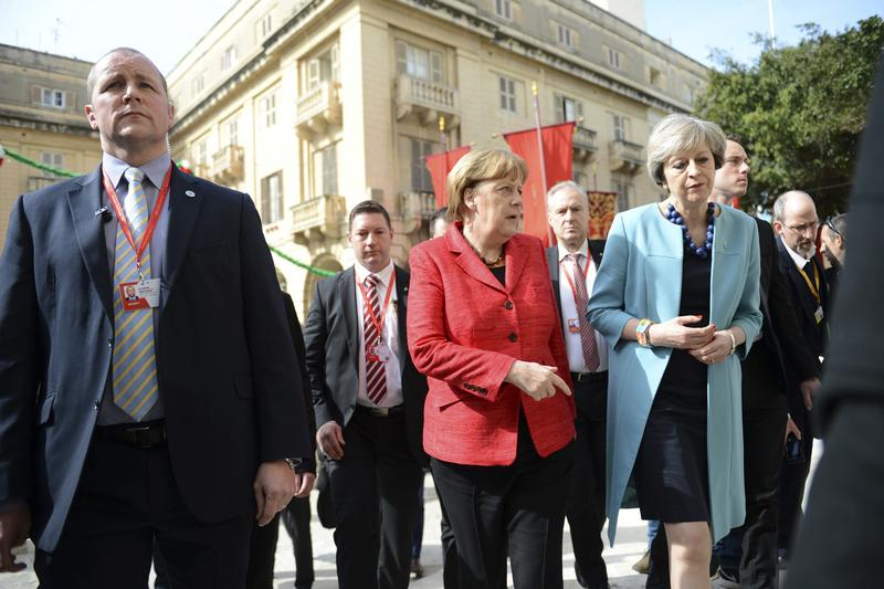 German Chancellor Angela Merkel, center, speaks with British Prime Minister Theresa May, right, as they walk with other EU leaders during an event at an EU summit in Valletta, Malta.(Rene Rossignaud/AP)