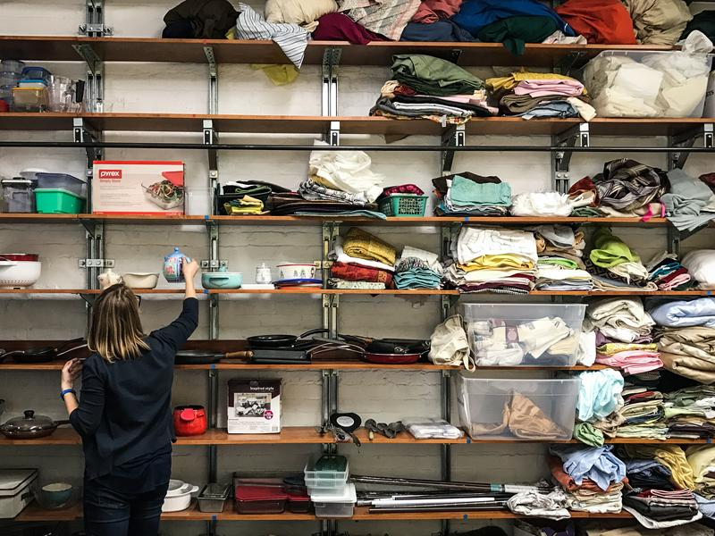 Betsy Jenson sorts through donated kitchenware, bed sheets and other household goods inside a storage area for the Nationalities Service Center in Philadelphia. The refugee resettlement agency uses donations to furnish apartments for newly arrived refugees.