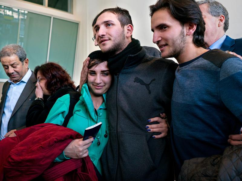 Tawfik Assali (center) of Allentown, Pa., embraces his sister, Sarah Assali, upon her and other family members' arrival from Syria at John F. Kennedy International Airport in New York Monday.