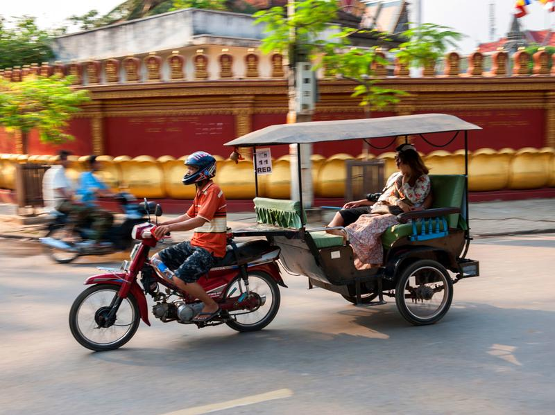 A tuk-tuk speeds down an urban Cambodian road. One deportee used his English language skills — and sense of humor — to build a successful tuk-tuk tour business.