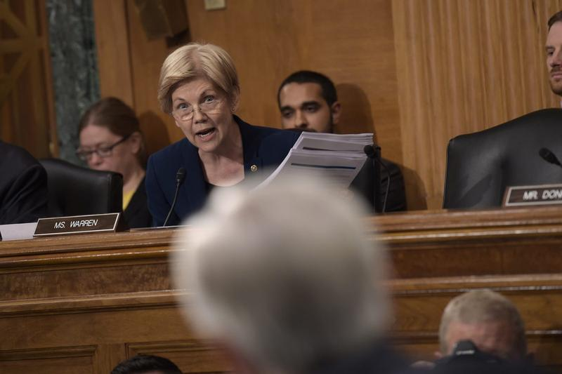 In this file photo, Senate Banking Committee member Elizabeth Warren holds up transcripts of earnings calls as she questions Wells Fargo CEO John Stumpf on Capitol Hill. (Susan Walsh/AP)