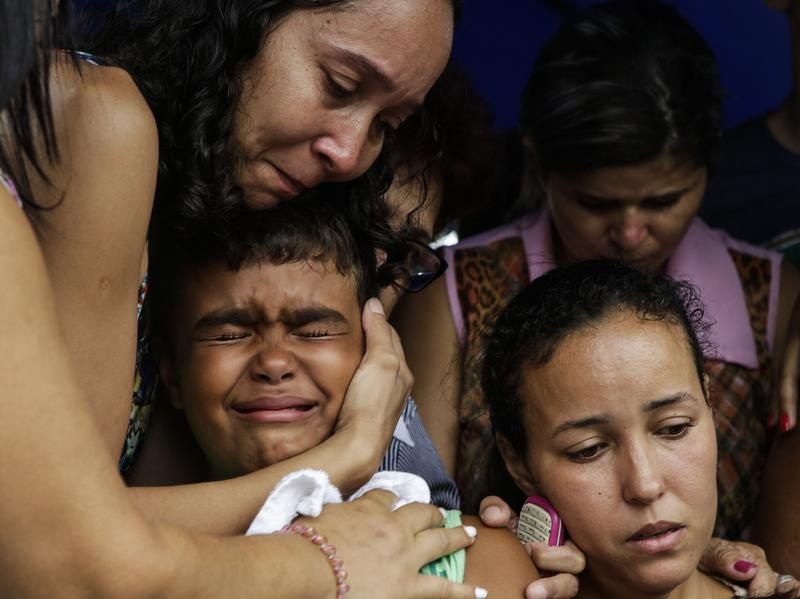 Kailua (center), son of slain civil police officer Mario Marcelo de Albuquerque Espirito, is comforted during his father's funeral on Wednesday in Serra, Espirito Santo state, Brazil. Mario Marcelo de Albuquerque was shot to death when he tried to impede a robbery.