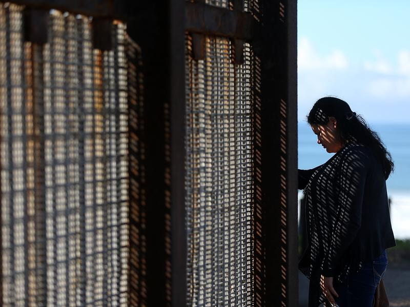 A visitor stands next to the U.S.-Mexico border fence at Friends of Friendship Park on Feb. 4 in San Ysidro, Calif.