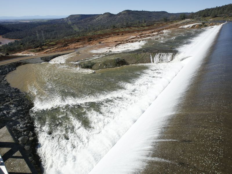 Water flows over the emergency spillway at Oroville Dam Saturday in Oroville, Calif.