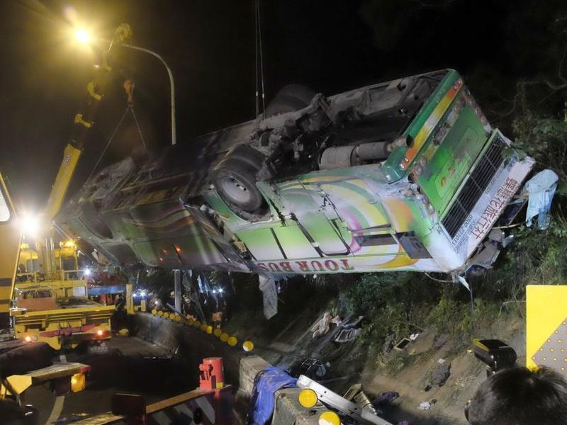 A bus that crashed along a highway is lifted by a crane on Tuesday in Taipei, Taiwan.
