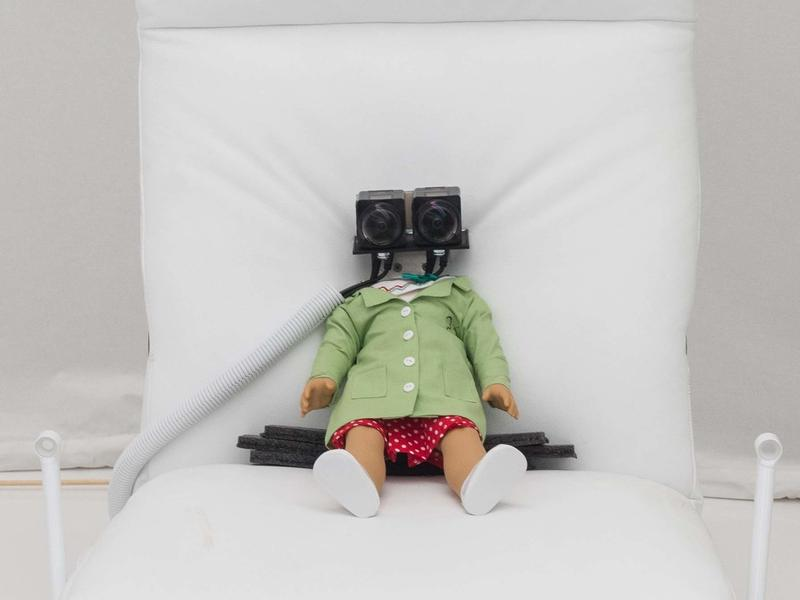 """A virtual reality installation allows visitors to experience a doll's perspective as she's poked and prodded by a lab assistant. <strong><a href=""""https://ww2.kqed.org/arts/2016/10/25/david-byrnes-theatrical-thought-experiment-in-silicon-valley/"""">Read the full story at KQED.</a></strong>"""