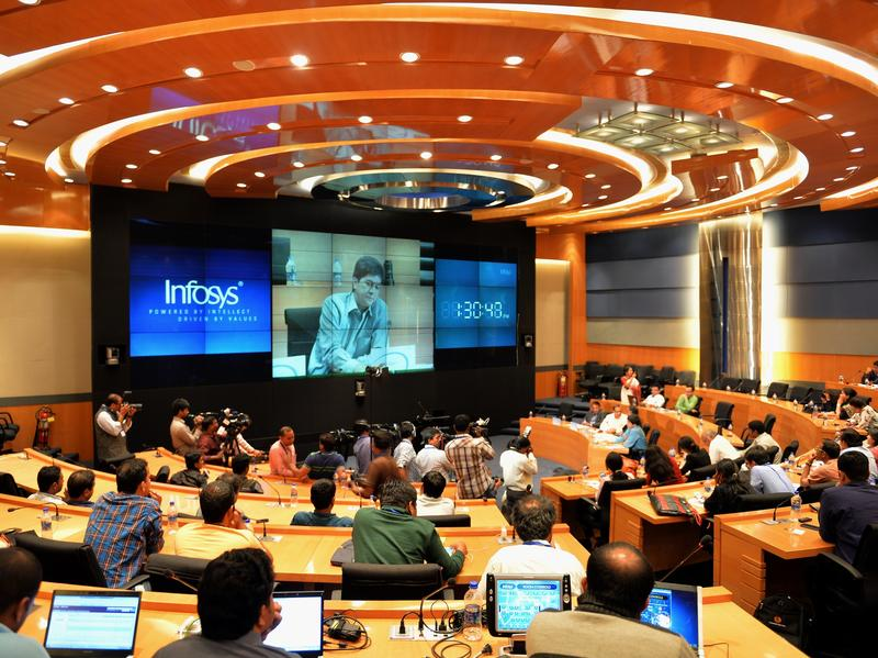 Members of the Indian media watch Rajiv Bansal, then the CFO of Infosys, during the announcement of the company's first quarter results in July 2014 in Bangalore. Indian software services firms draw tens of billions of dollars in revenue from U.S. contracts each year, and that's partly reliant exporting computer science talent on H1-B visas.