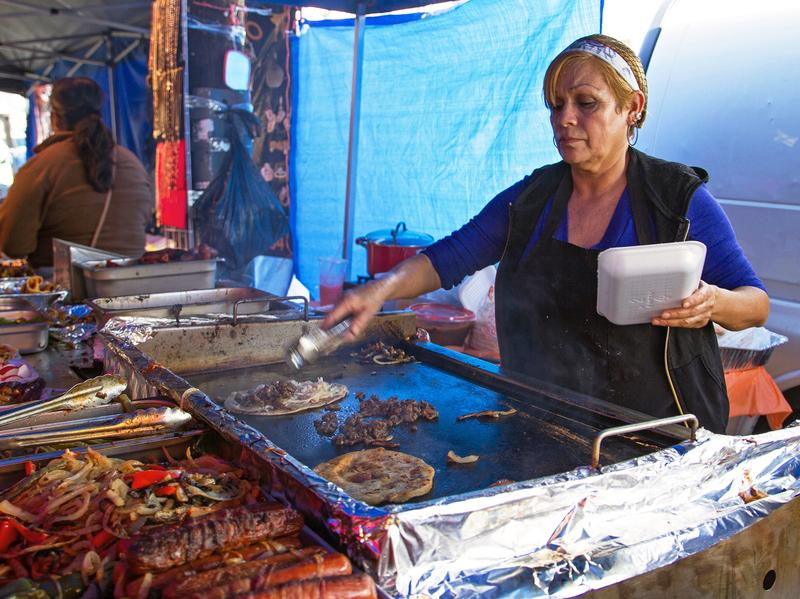 A street vendor makes <em>huaraches</em> and quesadillas on the sidewalk in the piñata district in Los Angeles. LA is the only major U.S. city where selling food on the sidewalk is illegal. President Trump's immigration policies have pushed the city council to change the law. But the devil is in the details.