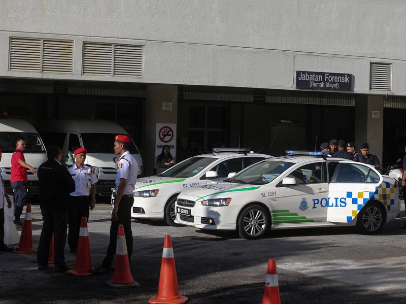 Malaysian police officers stand outside Putrajaya Hospital, outside Kuala Lumpur, where the body of Kim Jong Un's brother was initially brought.