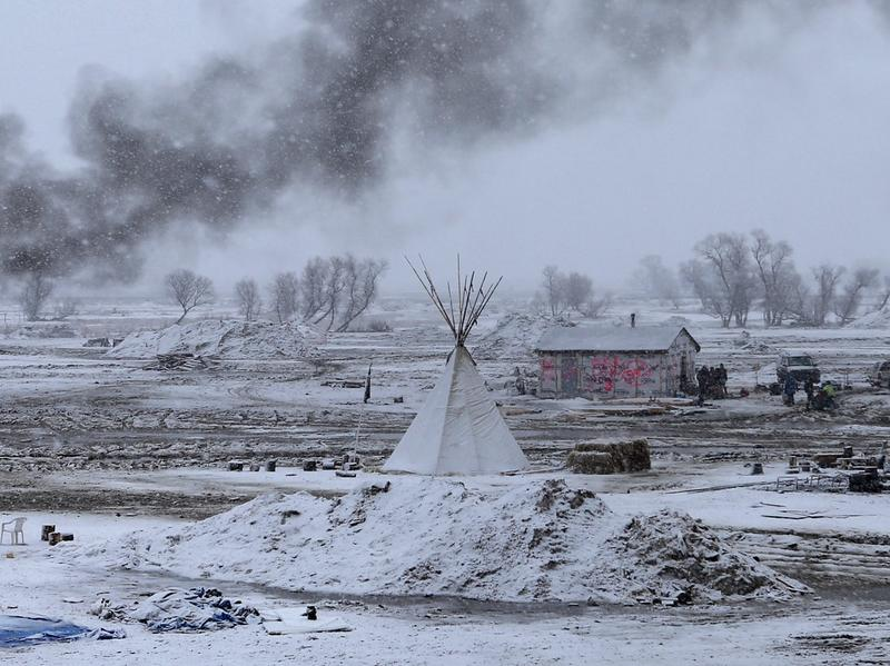 Snow falls on the Oceti Sakowin camp on Wednesday as structures smolder.