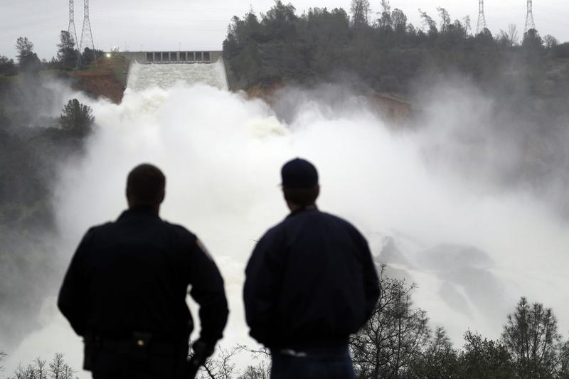 Two men watch as water gushes from the Oroville Dam's main spillway Wednesday, Feb. 15, 2017, in Oroville, Calif. (Marcio Jose Sanchez/AP)