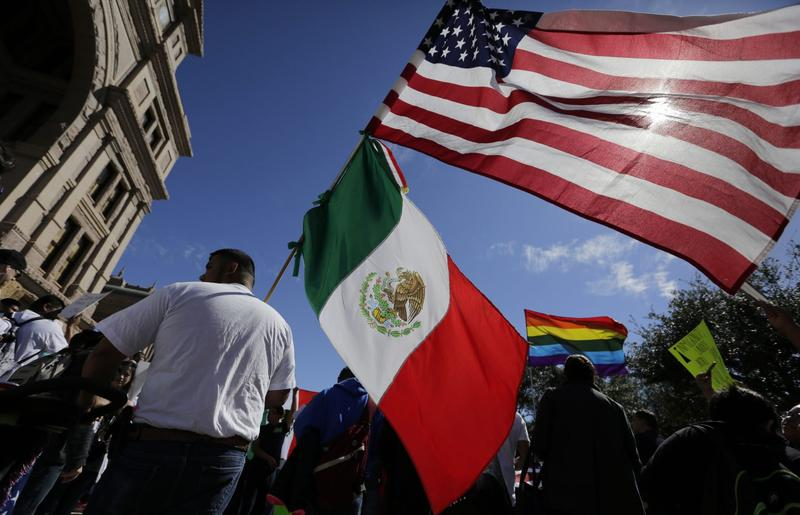 A man holds the U.S. and Mexico flags during a march and rally during an immigration protest, Thursday, Feb. 16, 2017, in Austin, Texas. (Eric Gay/AP)