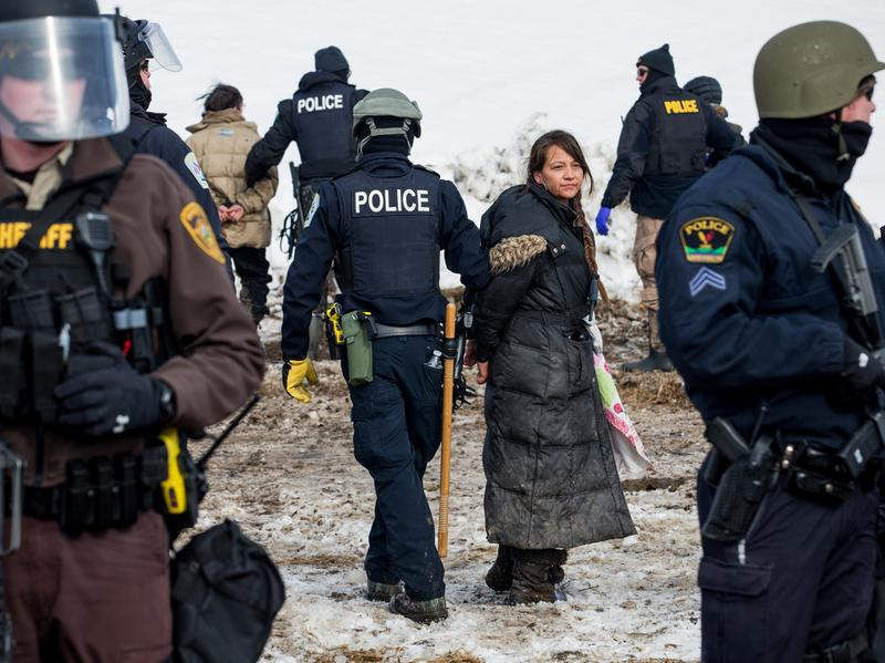 (Top) Police make arrests as they move through the Oceti Sakowin camp. (Bottom) The police moved steadily and slowly through the camp, accompanied by Humvees and maintaining a perimeter of the cleared area.