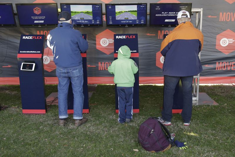 In this file photo, adults as well as kids enjoy a racing video game at the NASCAR Acceleration Nation interactive display at Daytona International Speedway. (John Raoux)