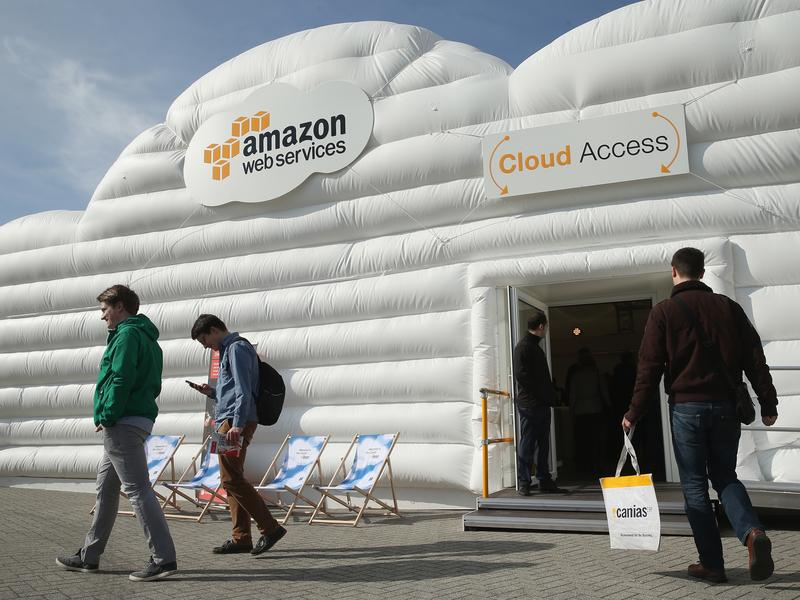 Visitors arrive at the cloud pavilion of Amazon Web Services at the 2016 CeBIT digital technology trade fair on March 14, 2016 in Hanover, Germany.