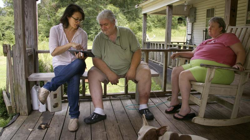 """Filmmaker Jennifer Crandall (left) sits with Billy Wayne Corkerin and his wife Lucy Corkerin on the porch of their home in Fayette, Ala. The couple read verse 43 of the Walt Whitman poem """"Song of Myself"""" for the project """"Whitman, Alabama."""" (Courtesy Pierre Kattar)"""