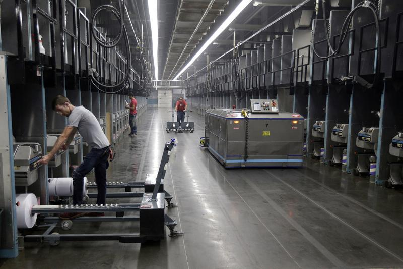 Workers exchange spools of thread as a robot picks up thread made from recycled plastic bottles at the Repreve Bottle Processing Center, part of the Unifi textile company in Yadkinville, N.C. (Chuck Burton/AP)