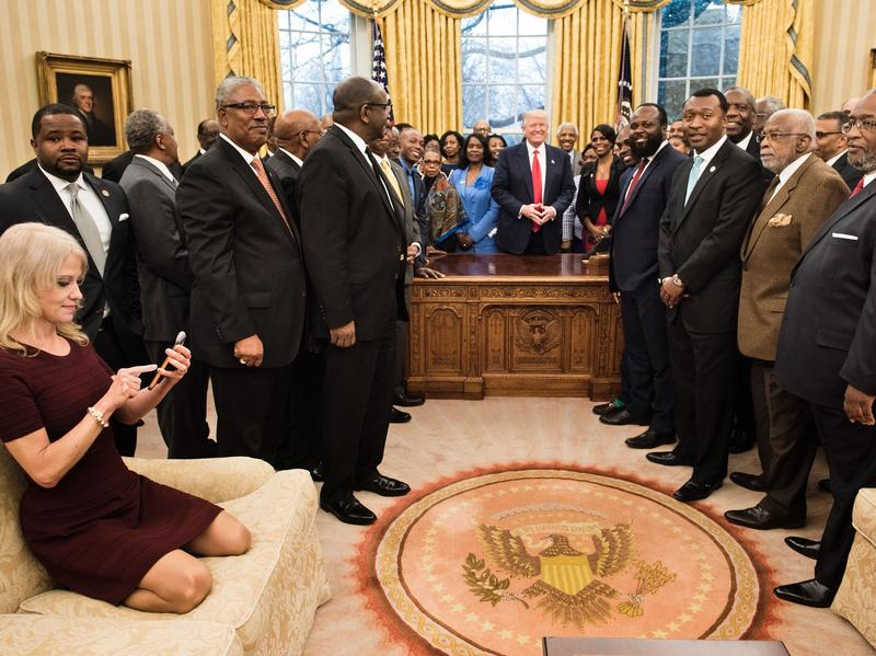 Counselor to the President Kellyanne Conway, left, checks her phone Tuesday after taking a photo as President Trump and leaders of historically black colleges and universities pose for a group photo in the Oval Office.
