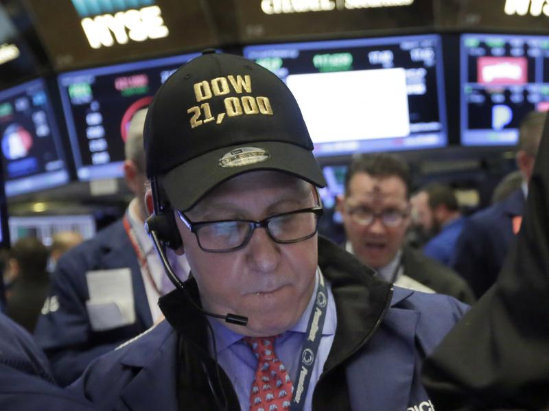 """Trader Richard Cohen wears a """"Dow 21,000"""" cap as he works on the floor of the New York Stock Exchange on Wednesday."""