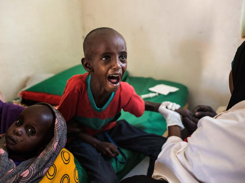A 5-year-old child cries as a nurse struggles to find a vein for an injection at a health clinic last month in Shada, Somalia. The child's family lost all their animals to drought and traveled more than 100 miles in search of a better situation.