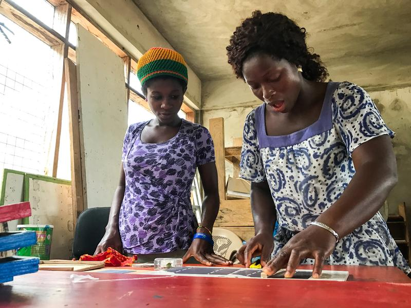 """Judith Ausah (left) and Evelyn Sewodey create solar panels at the Lady Volta Vocational Center for Electricity and Solar Power in Ghana. """"At first, I thought it was man's work,"""" says Ausah, whose 2-month-old daughter stays in the school nursery. """"But I came here and saw that, yes, women can do it."""""""