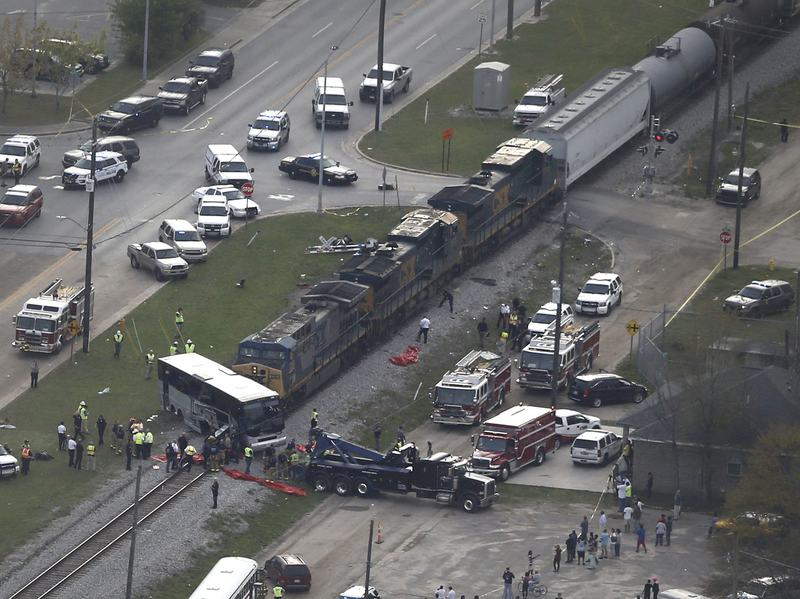 Emergency crews work on the scene where a train hit a charter bus in Biloxi, Miss., Tuesday. The National Transportation Safety Board says the freight train was traveling about 19 mph at the time of the crash.