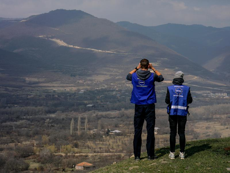 Members of the European Union Monitoring Mission peer through binoculars at the boundary line between Georgia and South Ossetia.