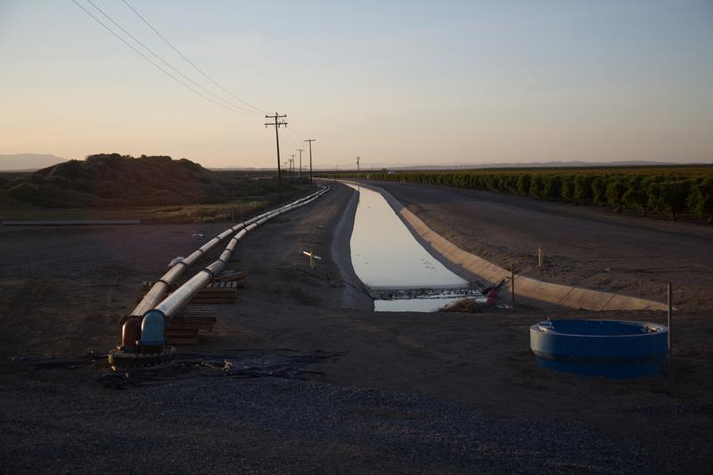 """A still image from the documentary """"Water and Power,"""" showing a pipeline allegedly owned by Stewart Resnick, bringing water from Dudley Ridge to Lost Hills. (Courtesy Ted Gesing/National Geographic)"""