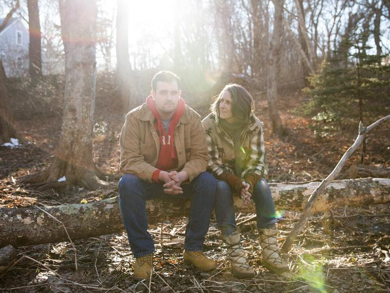 Tucker Lane and his mother, Lynn Cash, sit in the wooded backyard of his home in West Barnstable, Mass.