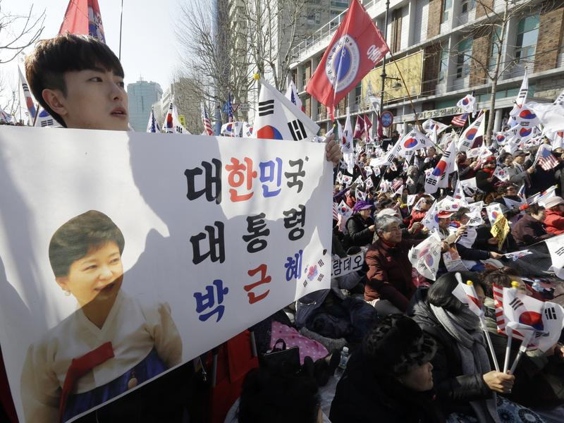 """Supporters of South Korean President Park Geun-hye stage a rally opposing her impeachment near the Constitutional Court in Seoul on Friday. People gathered ahead of the court ruling on whether Park would be removed from office over a corruption scandal. The sign reads """"South Korean President Park Geun-hye."""" Recent polling showed a 3-1 margin in favor of impeachment."""