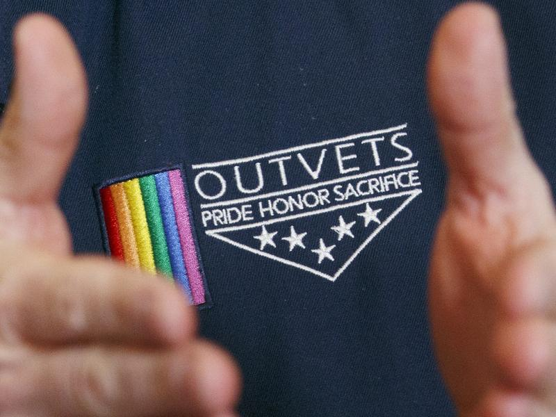 OutVets founder Bryan Bishop wears the logo of his group while speaking in Boston. The group has been invited to participate in the city's privately-run St. Patrick's Day parade.