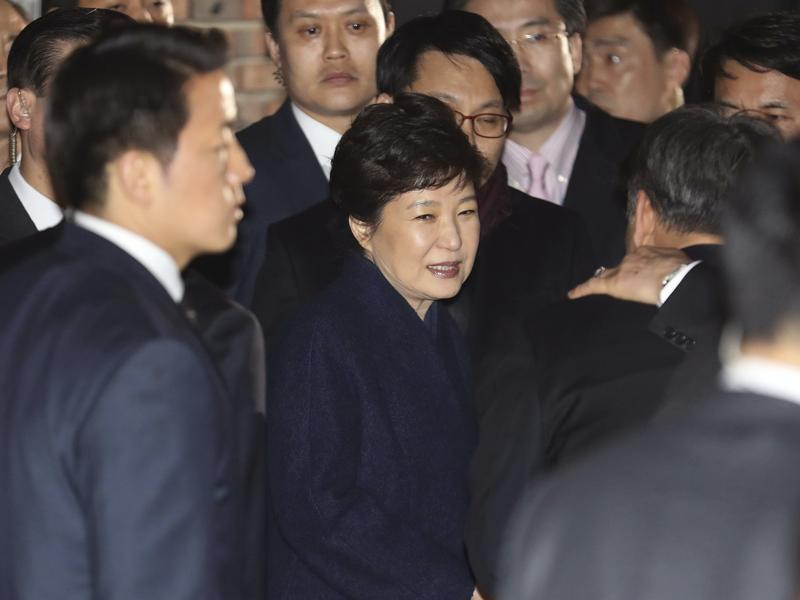 Ousted South Korea's former President Park Geun-hye, center, arrives at her private home in Seoul, South Korea, on Sunday. She vacated the presidential palace and returned to her home two days after the Constitutional Court removed her from office.
