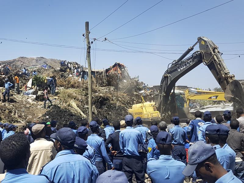 Police officers secure the perimeter at the scene of a garbage landslide, as excavators aid rescue efforts on the outskirts of Ethiopia's capital city, Addis Ababa, on Sunday.