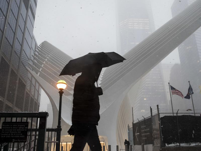 A man walks through snow during the morning commute in Manhattan on Tuesday.