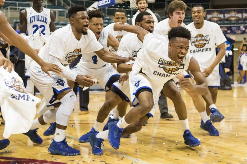 New Orleans' Matthew Jiles, front, runs to grab the championship trophy after the team defeated Texas A&M-Corpus Christi 68-65 in overtime in an NCAA college basketball game for the championship of the Southland Conference tournament Saturday, March 11, 2017, in Katy, Texas. (Joe Buvid/AP)
