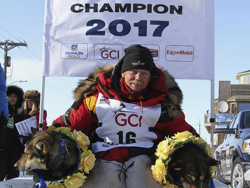 Mitch Seavey poses with his lead dogs Pilot, left, and Crisp under the Burled Arch after winning the 1,000-mile Iditarod Trail Sled Dog Race, in Nome, Alaska, on Tuesday. Seavey won his third Iditarod, becoming the fastest and oldest champion at age 57.