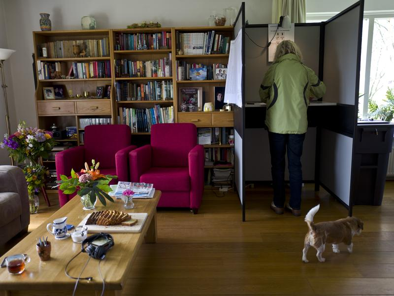 In a living room in the Westhoff family's house in the Dutch town of Marle, a woman fills out her ballot in Wednesday's national elections. The family also runs a bed and breakfast out of their farm house.