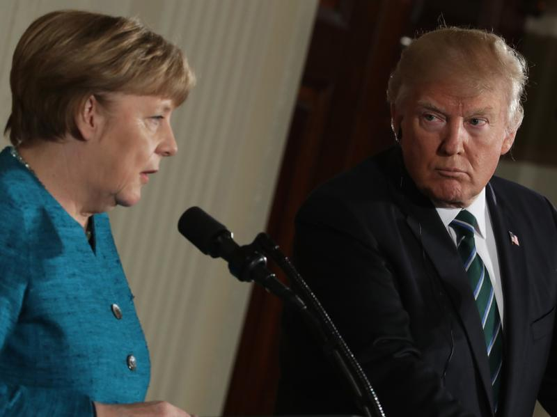 President Trump looks on as German Chancellor Angela Merkel addresses the media at a joint news conference Friday at the White House.