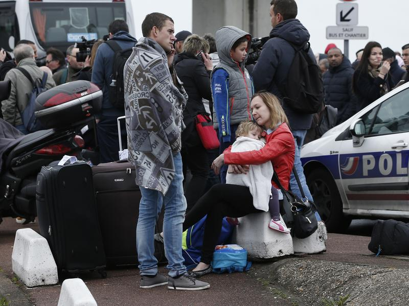 Travelers wait outside the Orly airport, south of Paris, Saturday, March, 18, 2017.