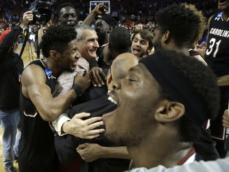 South Carolina head coach Frank Martin, second from left, is hugged by Chris Silva, left, as they celebrate after a second-round game against Duke in the NCAA men's college basketball tournament in Greenville, S.C., on Sunday.