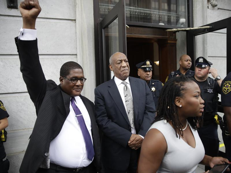 Bill Cosby looks on as spokesman Andrew Wyatt triumphantly raises his fist outside the Montgomery County Courthouse in Norristown, Pa., on Saturday. Cosby's legal and publicity team treated the mistrial as a victory, though prosecutors immediately said they plan to retry the case.