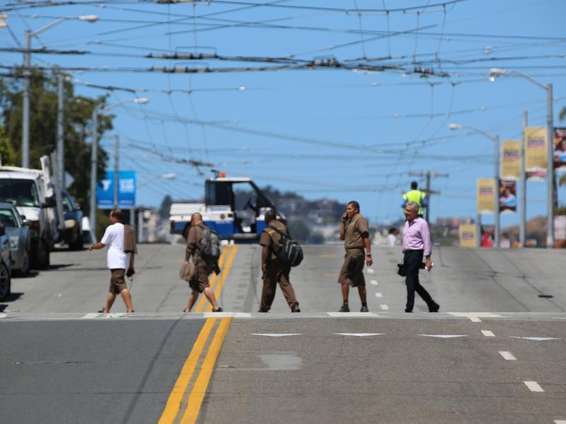 UPS employees cross the street shortly after a shooting at the company's facility in San Francisco. According to law enforcement, the suspect killed himself with a gunshot to the head.