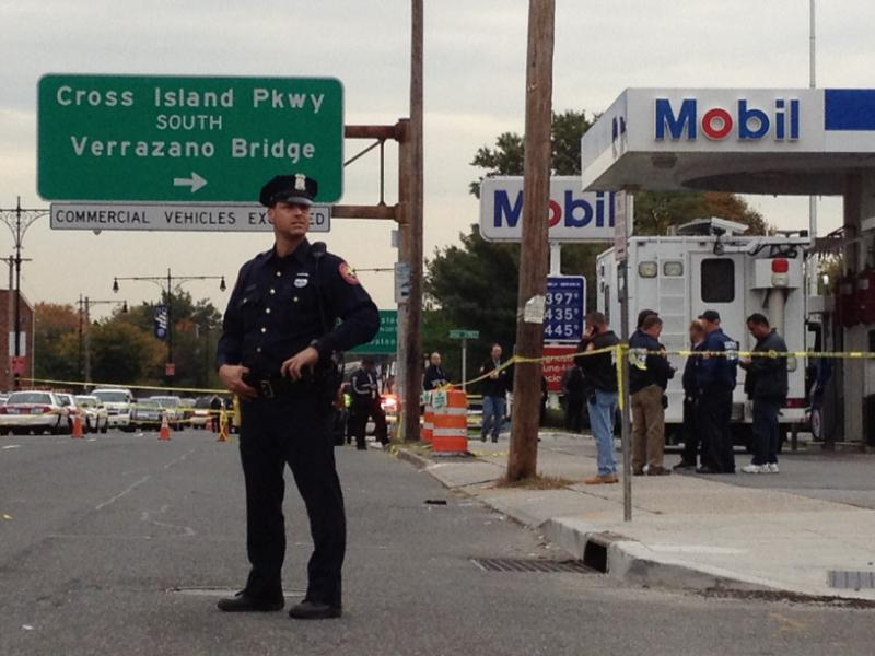 A police officer stands near the scene of a shooting that left a Nassau County police officer and civilian dead.