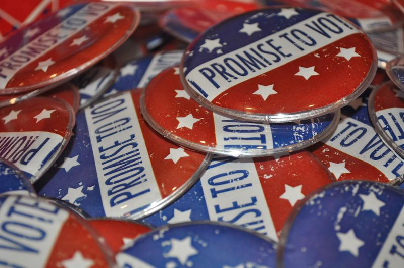 'I Promise to Vote' pins.