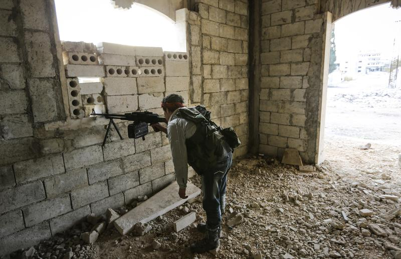 A rebel machine gunner watches Syrian army positions 500 metres away in the town of Maarat al-Numan, on November 17, 2012.