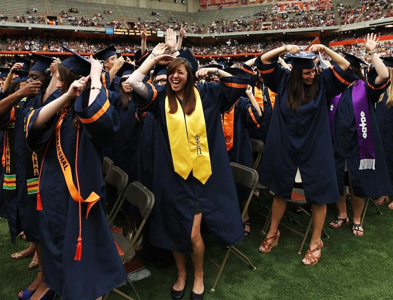 Graduates high-five at the 2012 Syracuse University commencement.  Economists tell us that degrees lead to higher pay and a happier life, but how does college actually produce those gains?