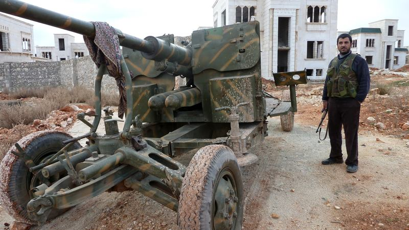A fighter stands close to a gun in the Sheikh Suleiman base, some 15 miles northwest of the city of Aleppo on December 9, 2012.