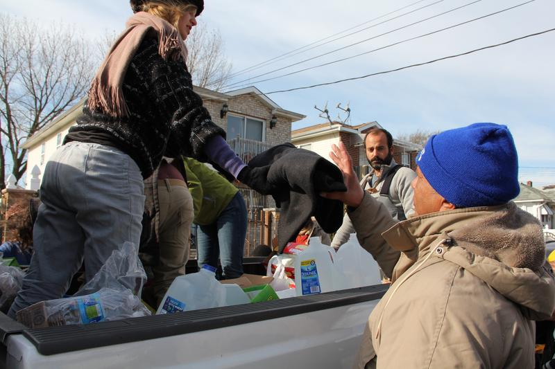 A volunteer hands a man a blanket, as Chris Parachini, center, looks on.