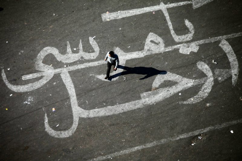 An Egyptian man walks over a graffiti reading 'Morsi Go' on November 25, 2012 at Egypt's landmark Tahrir square in Cairo.